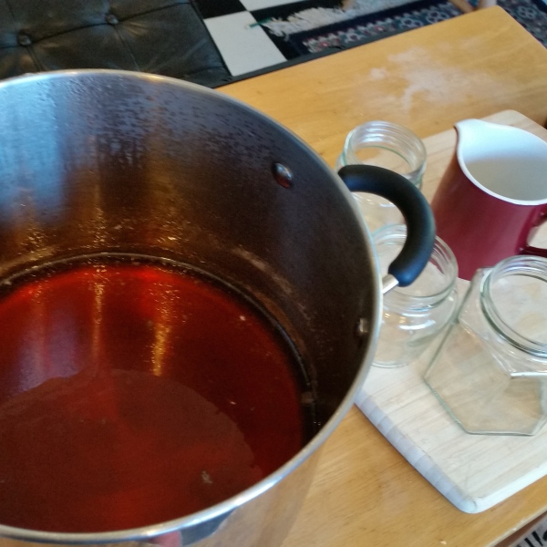 I carefully place the hot jam onto a wooden board , with jars and a jug that has been pre-warmed.
